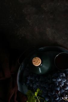 Mazzo scuro di uva con gocce d'acqua in condizioni di scarsa luminosità, vino rosso, foto scura con spazio di copia