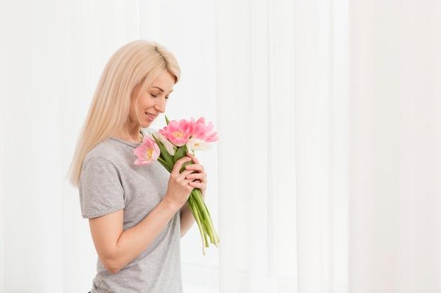 Mazzo sentente l'odore dei fiori della donna di vista laterale