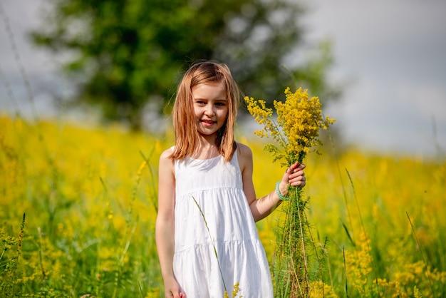 Mazzo sveglio del wildflower della holding della bambina
