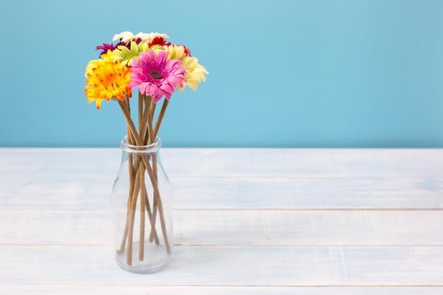 Mazzo variopinto dei fiori in chiara bottiglia sulla tavola blu-chiaro davanti alla parete blu. visualizza con copia spazio