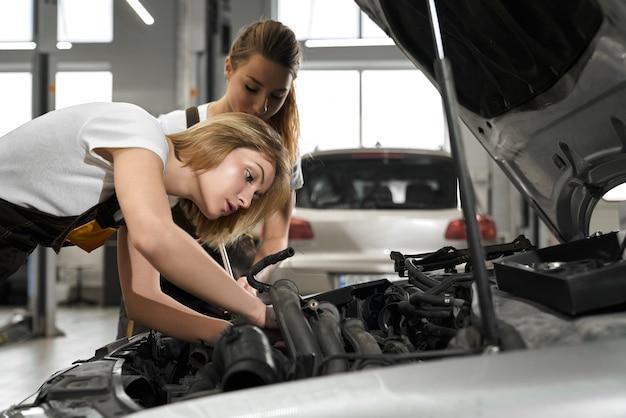 Meccanica di due ragazze e automobile di riparazione.