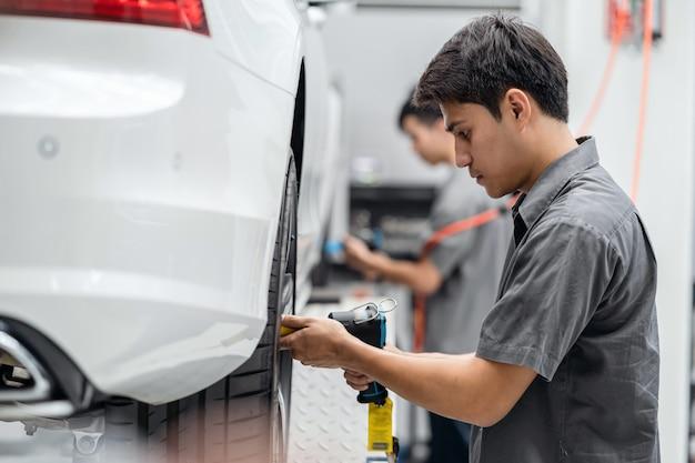 Meccanici asiatici che controllano le ruote di automobile al centro di servizio di manutenzione per nella sala d'esposizione