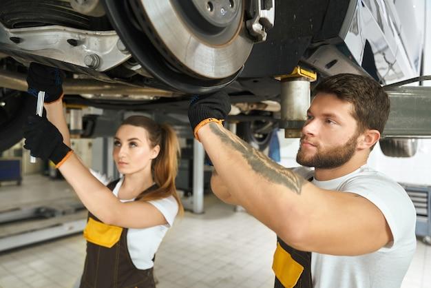 Meccanici della donna e dell'uomo che riparano il telaio dell'automobile.