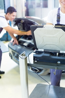 Meccanici di automobile con lo strumento di diagnosi nell'officina automatica asiatica