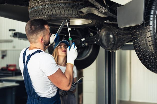 Meccanici di servizio dell'automobile di vista frontale che riparano automobile