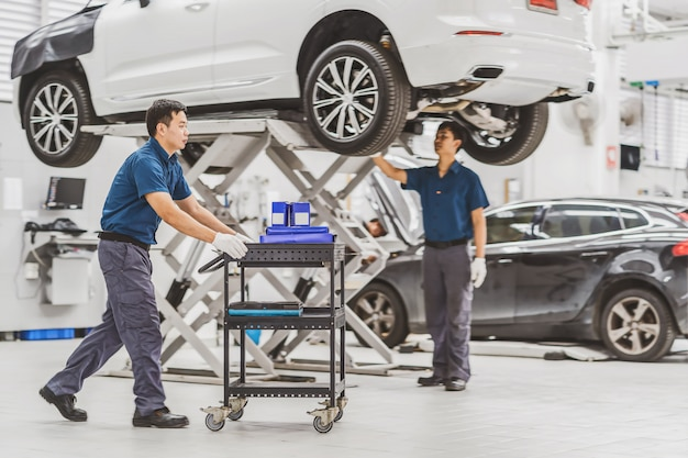 Meccanico asiatico spingere il carrello con attrezzature per auto sul collega controllo e riparazione della vettura