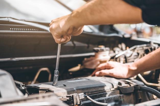 Meccanico auto che lavora in garage tecnico mani del meccanico di auto che lavora in auto riparazione