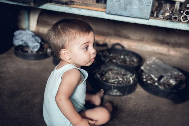 Meccanico baby boy - seduto sul pavimento di un negozio