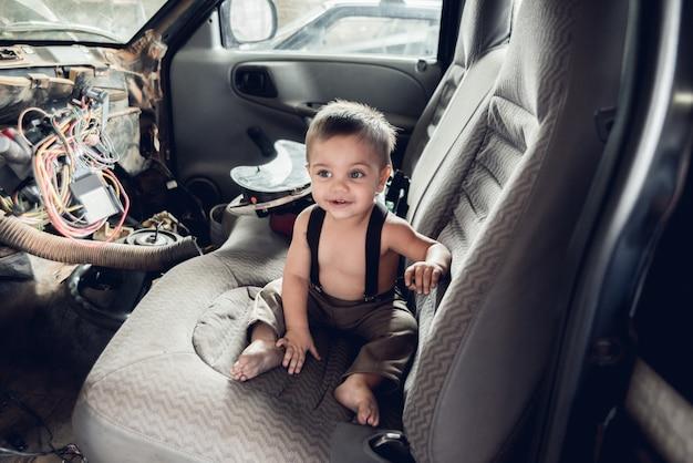 Meccanico baby boy - seduto sul vecchio sedile dell'auto