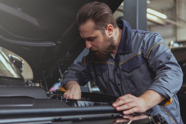 Meccanico barbuto che lavora alla stazione di servizio dell'automobile