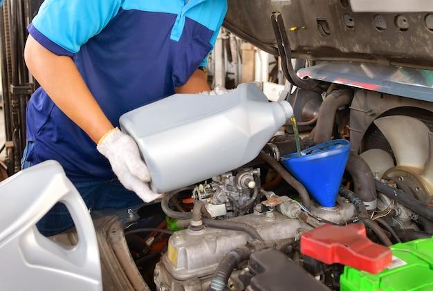 Meccanico che aggiunge olio per motori per la qualità nell'automobile del motore trasmissione e manutenzione gear.energy fuel concept.