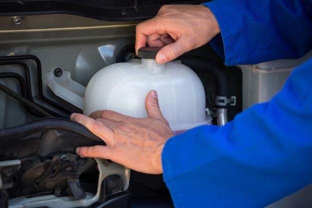 Meccanico che controlla un serbatoio di acqua di raffreddamento
