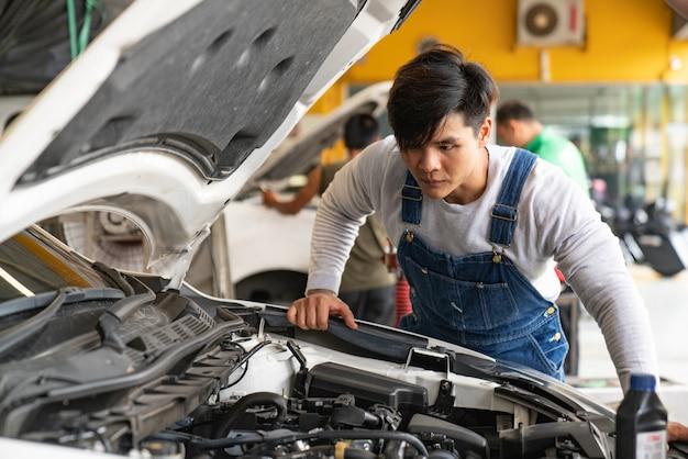 Meccanico che lavora al motore nell'officina riparazioni automatica