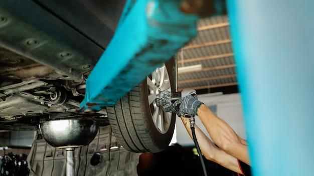 Meccanico che lavora il suo lavoro. auto sulla macchina di sollevamento presso la stazione di riparazione auto. servizi di riparazione e manutenzione. messa a fuoco selettiva