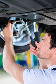 Meccanico che lavora nell'officina dell'automobile sulla ruota