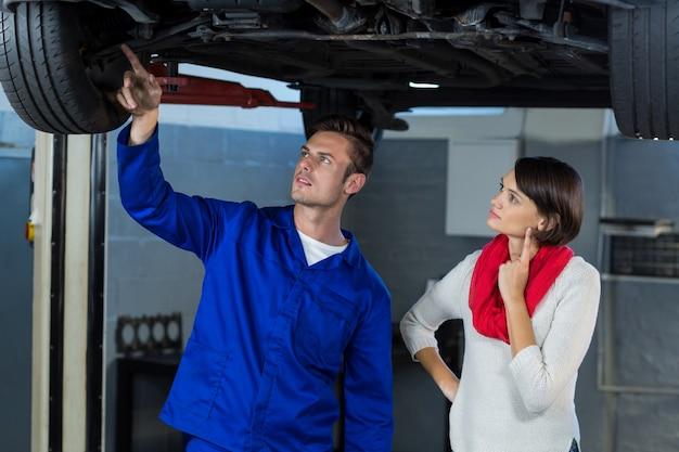 Meccanico che mostra cliente il problema con la macchina