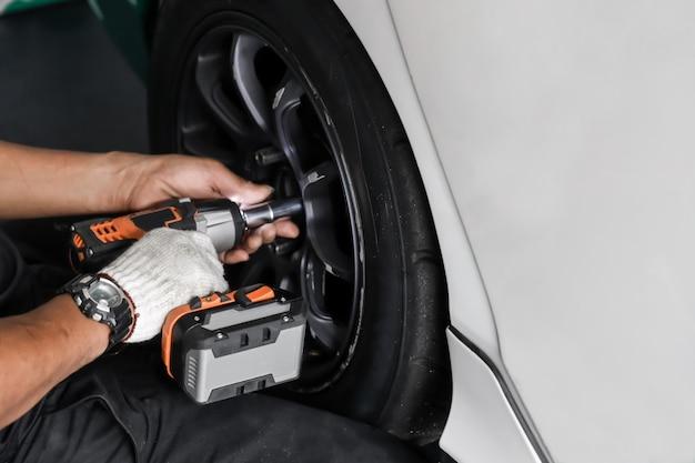 Meccanico che ripara gomma nel negozio di automobili