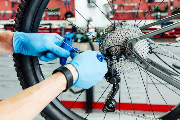 Meccanico che ripara il cambio della bicicletta in officina