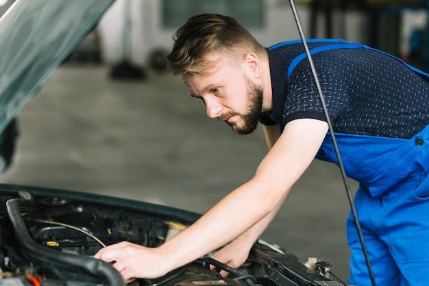 Meccanico che ripara il motore dell'automobile
