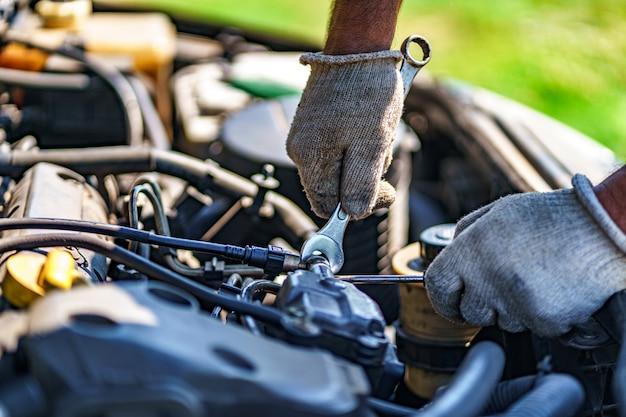 Meccanico che ripara un motore di automobile. servizio di riparazione
