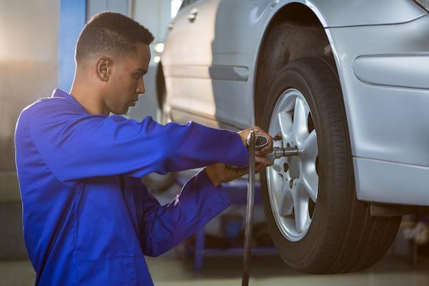 Meccanico che ripara una gomma di automobile