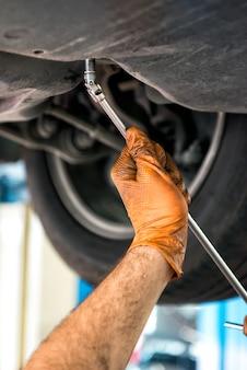 Meccanico che usando una chiave su un'automobile