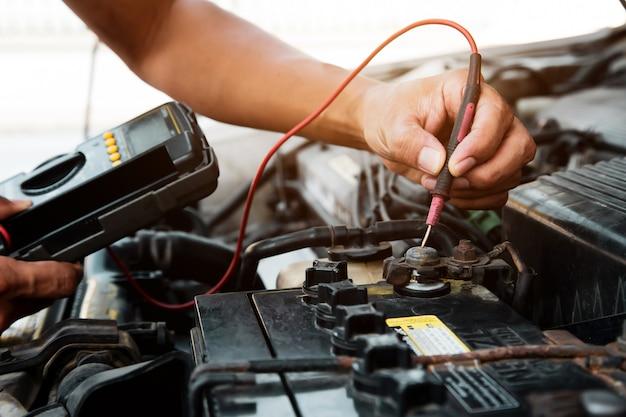 Meccanico che utilizza lo strumento dell'attrezzatura di misurazione per controllare la batteria dell'automobile.