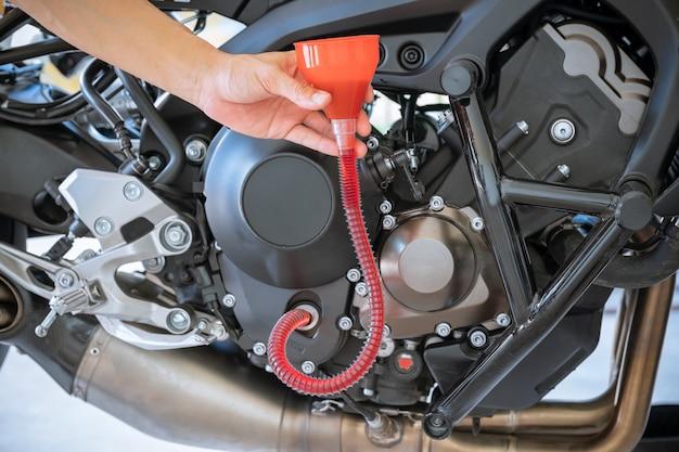 Meccanico che versa olio fresco versato durante il cambio dell'olio sul motore del motociclo