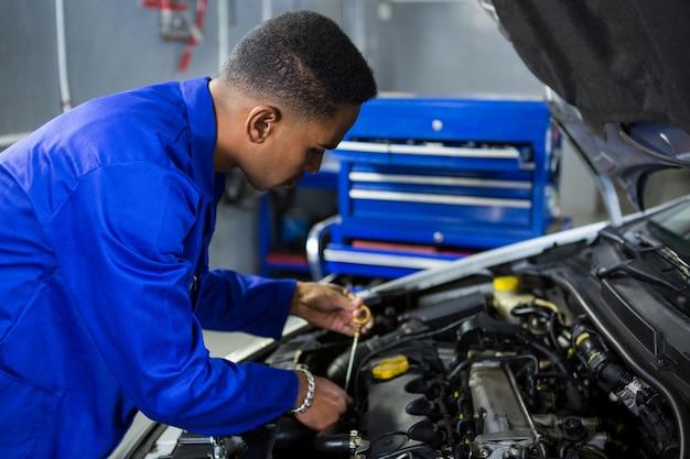 Meccanico controllare il livello dell'olio nel motore di un'auto