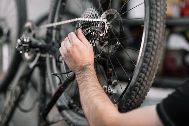 Meccanico della bicicletta in un'officina nel processo di riparazione.