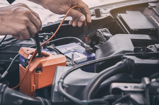 Meccanico della mano del primo piano che usando lo strumento dell'attrezzatura di misurazione per il controllo della batteria dell'automobile.