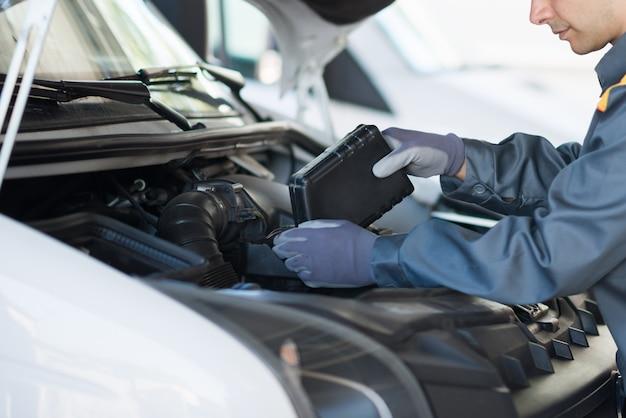 Meccanico di auto che mette olio in un motore di furgone