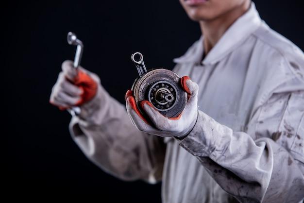 Meccanico di automobile che indossa una chiave della tenuta del supporto dell'uniforme bianca