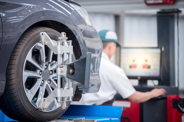 Meccanico di automobile che installa sensore durante la regolazione delle sospensioni. lavori di allineamento delle ruote presso la stazione di servizio di riparazione