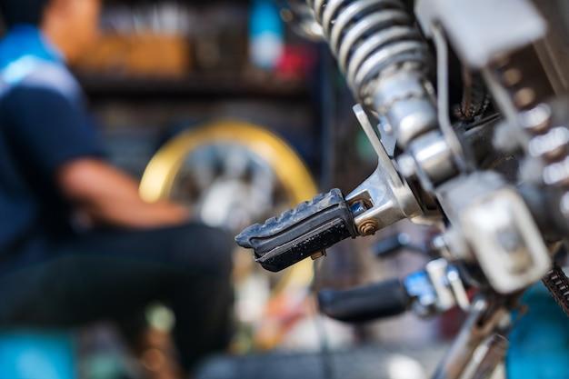 Meccanico di automobile che ripara motociclo nell'officina riparazioni della bici