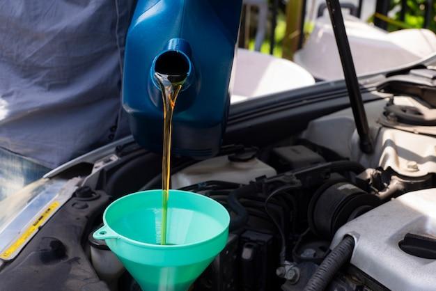 Meccanico di automobile che sostituisce e che versa olio fresco nel motore alla riparazione di manutenzione