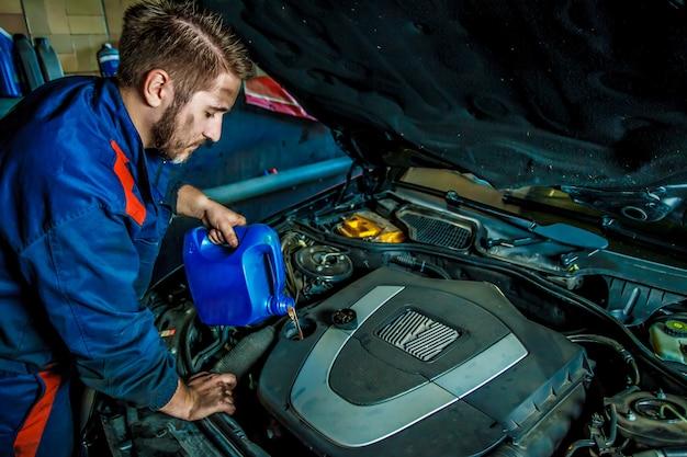 Meccanico di automobile che sostituisce e che versa olio nel motore alla stazione di servizio di riparazione di manutenzione.
