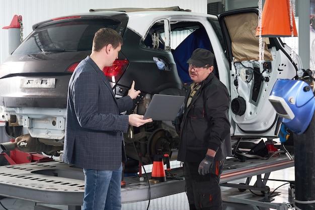 Meccanico e tecnico che lavorano nell'officina riparazioni