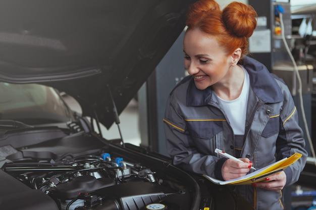 Meccanico femminile che lavora al distributore di benzina