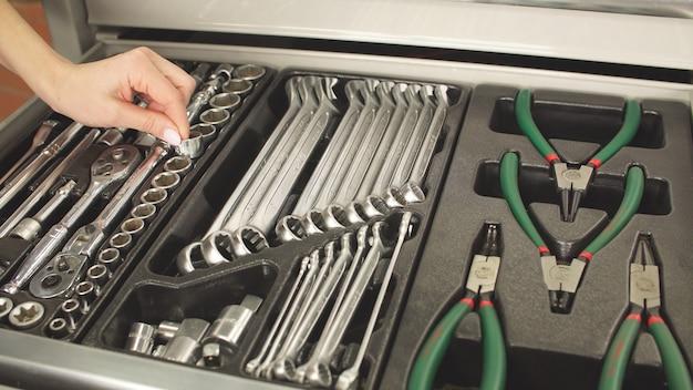 Meccanico femminile con manicure sceglie lo strumento necessario per il lavoro