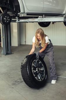 Meccanico femminile dell'angolo alto che sostituisce la ruota di automobile