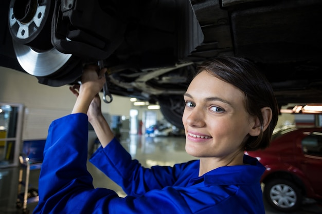 Meccanico femminile fissazione di un freno a disco ruota auto