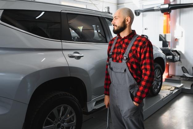 Meccanico maschio che lavora in un negozio di riparazioni e strumenti di contenimento