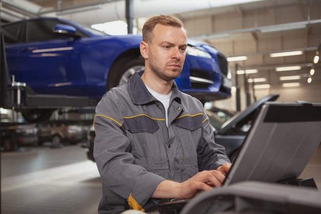 Meccanico maschio maturo che lavora al garage