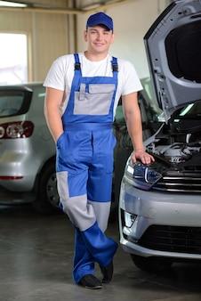 Meccanico nell'officina riparazioni automatica che sta accanto all'automobile.