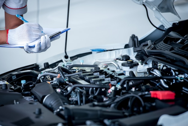 Meccanico (o tecnico) che controlla il motore di automobile nel garage