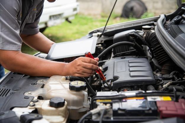 Meccanico professionista che controlla la ricerca del motore di automobile per i dati con la compressa