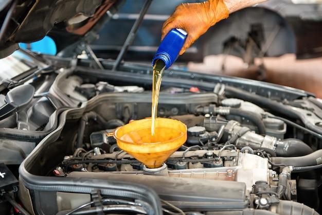 Meccanico rabboccare l'olio in una macchina