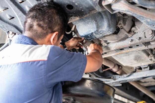 Meccanico uomo riparazione auto in garage e cambio olio motore. era in piedi sotto la macchina con la macchina dell'ascensore.