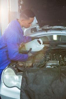 Meccanico versando olio lubrificante nel motore auto